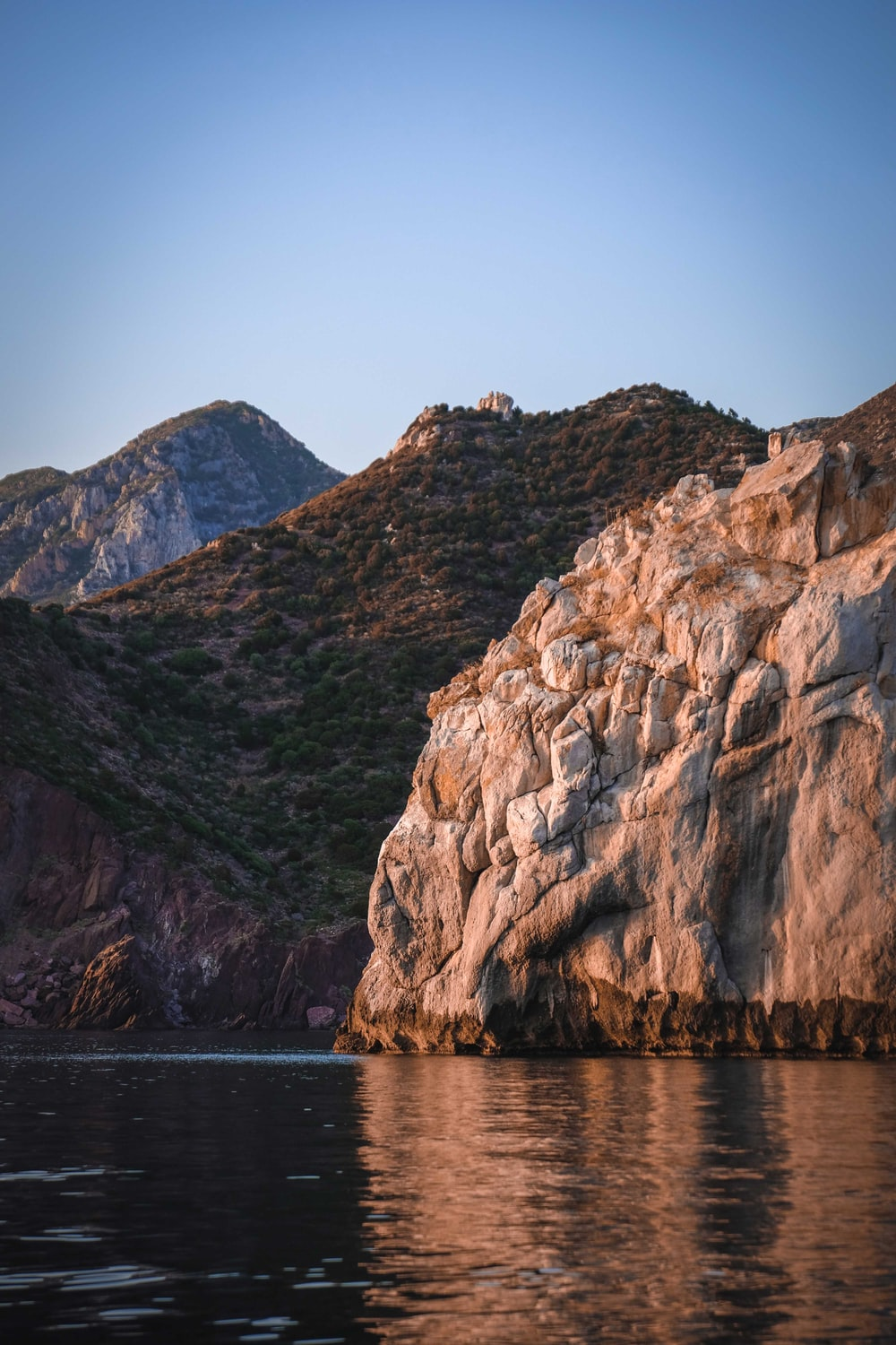 brown rocky mountain beside body of water during daytime
