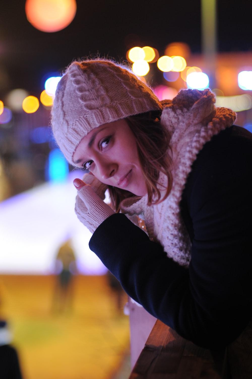woman in black long sleeve shirt wearing white knit cap