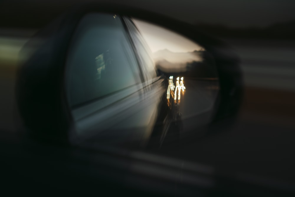 person in black jacket standing in front of car side mirror