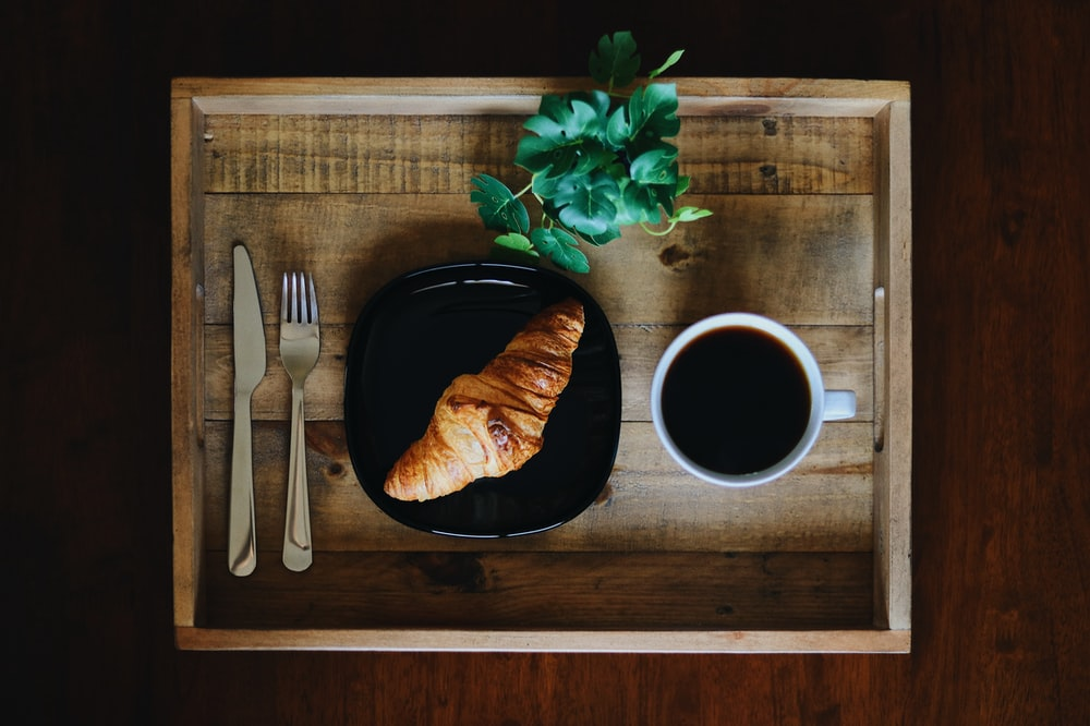 white ceramic mug beside stainless steel fork and bread knife on brown wooden chopping board