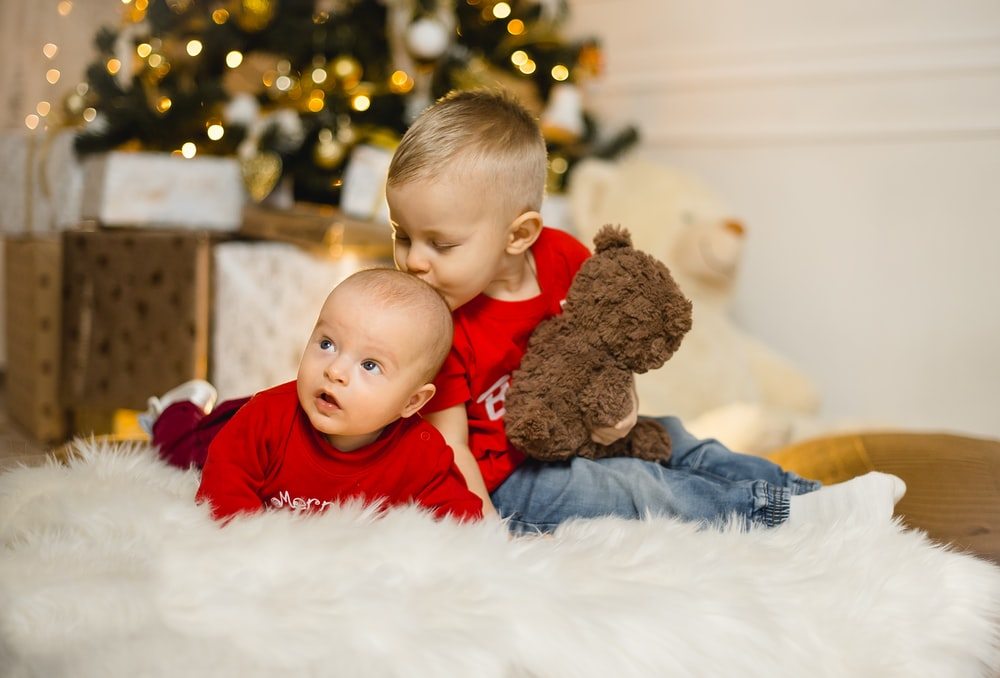 boy in red long sleeve shirt sitting on white fur textile