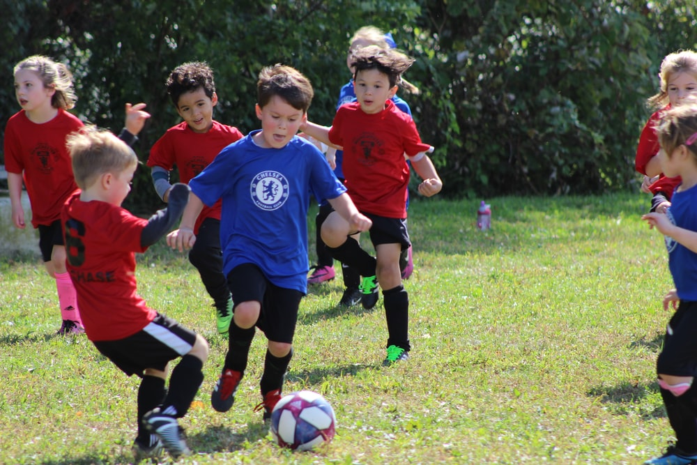 boy in red and blue soccer jersey kicking soccer ball on green grass field during daytime