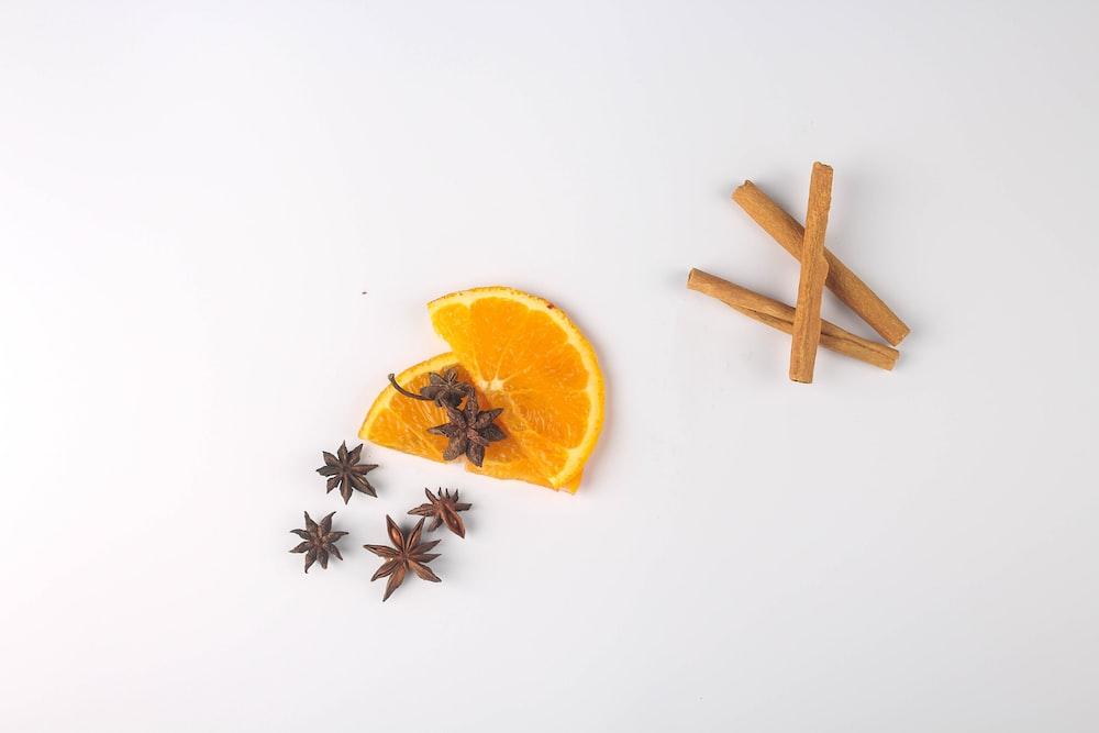 sliced orange fruit beside brown wooden stick