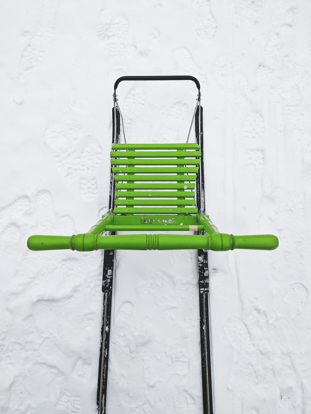 green and black folding chair on white snow
