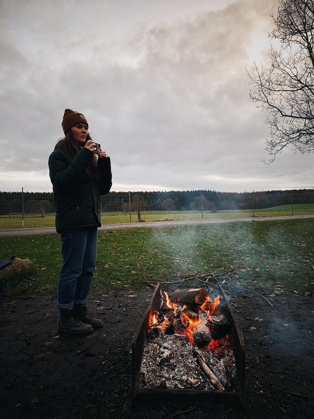 man in black jacket standing near bonfire during daytime