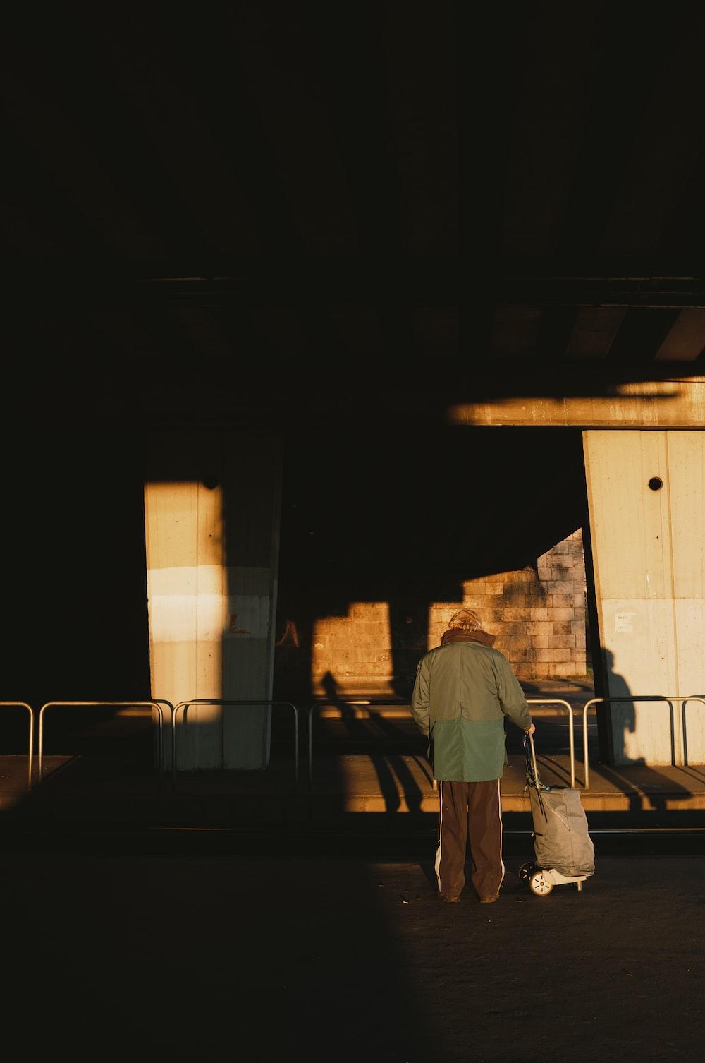 man in gray shirt and gray pants walking on sidewalk during daytime