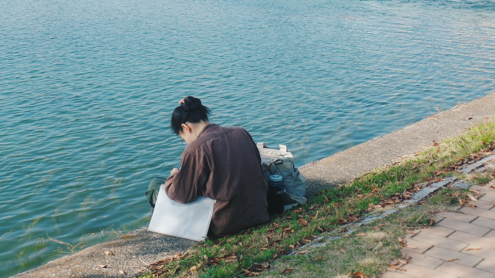 woman in brown shirt sitting on white concrete bench near body of water during daytime