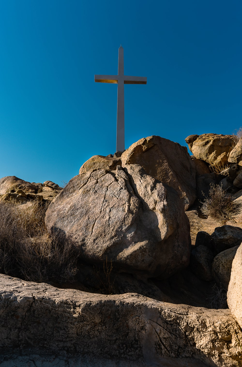 brown cross on brown rock formation under blue sky during daytime