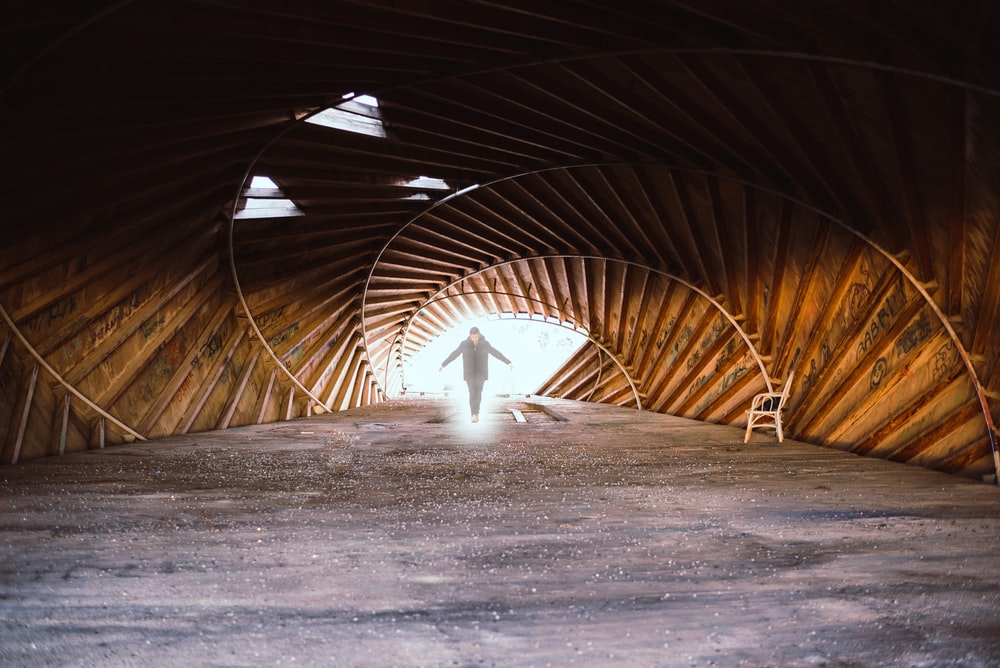 person in black jacket walking on tunnel
