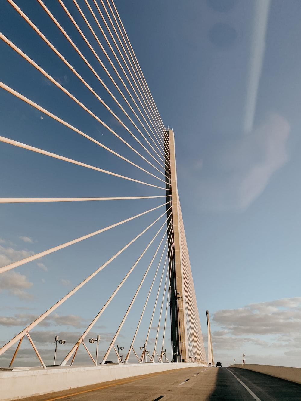 gray bridge under white clouds during daytime