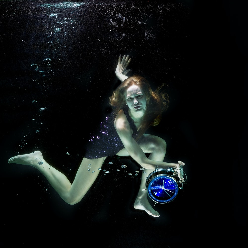 woman in blue and white bikini top and blue and white goggles under water