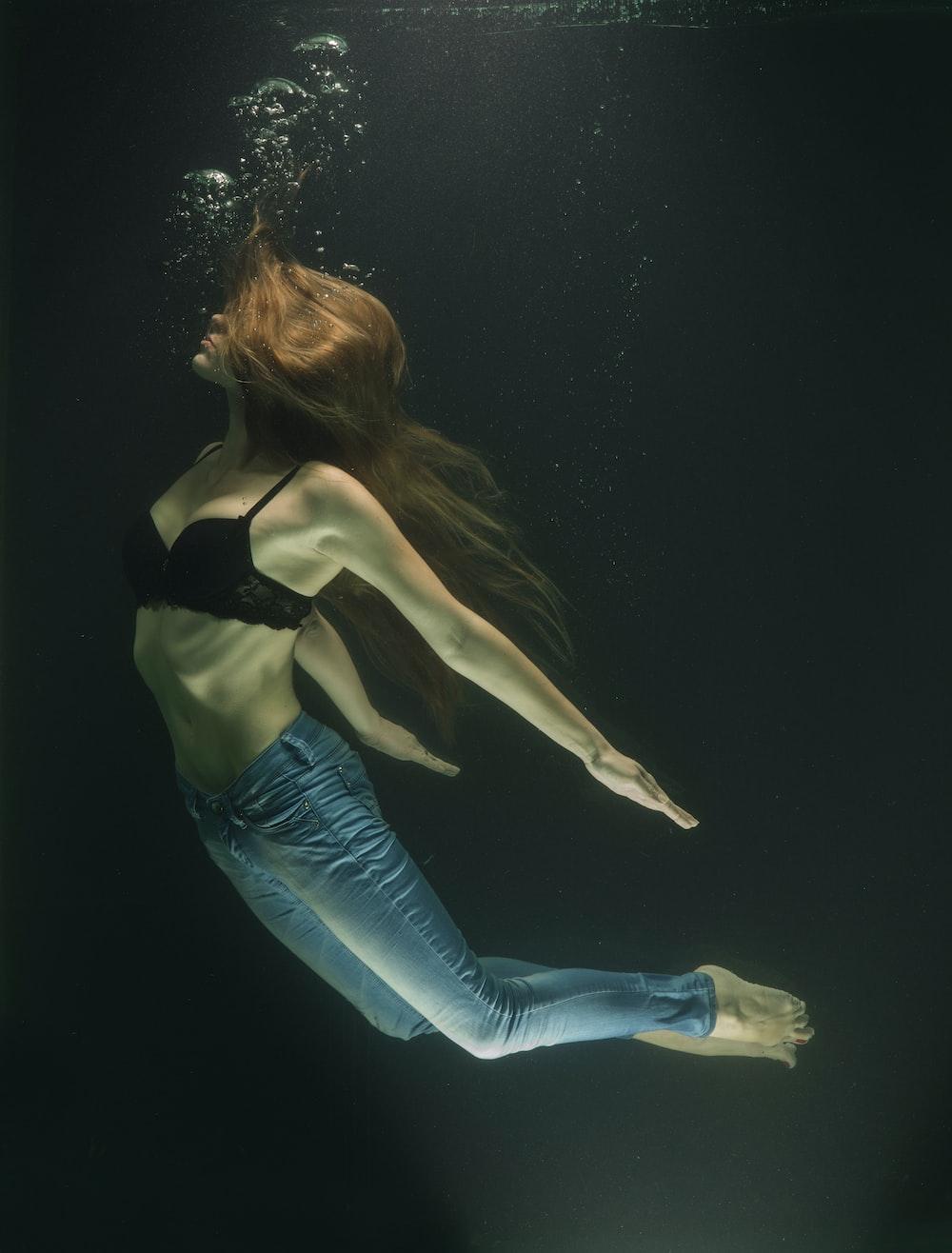 woman in black brassiere and blue denim jeans underwater