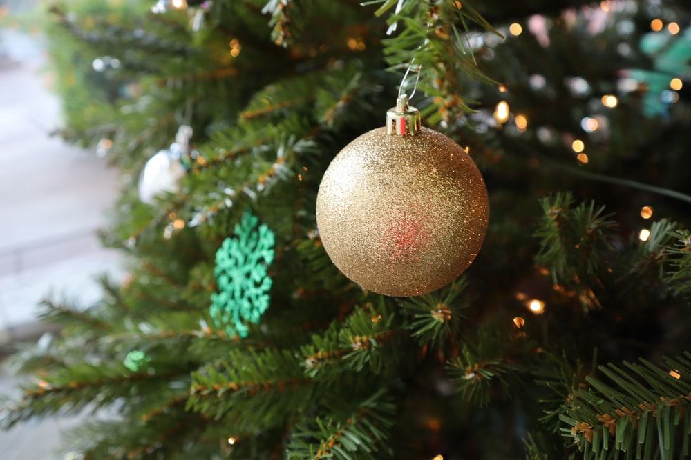 gold bauble hanging on green christmas tree