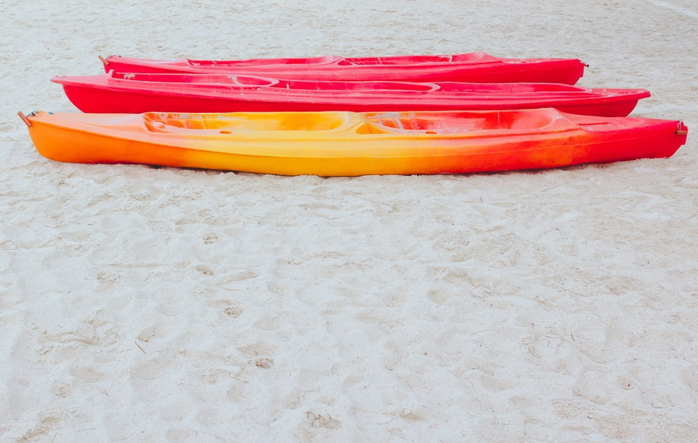 red and yellow kayak on white marble table