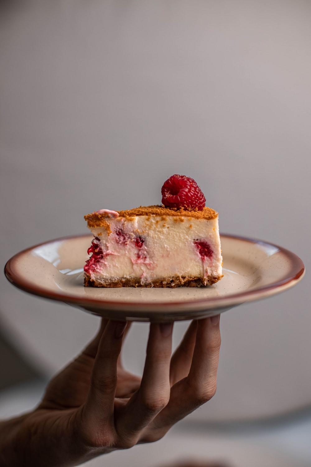 person holding strawberry cake on white ceramic plate