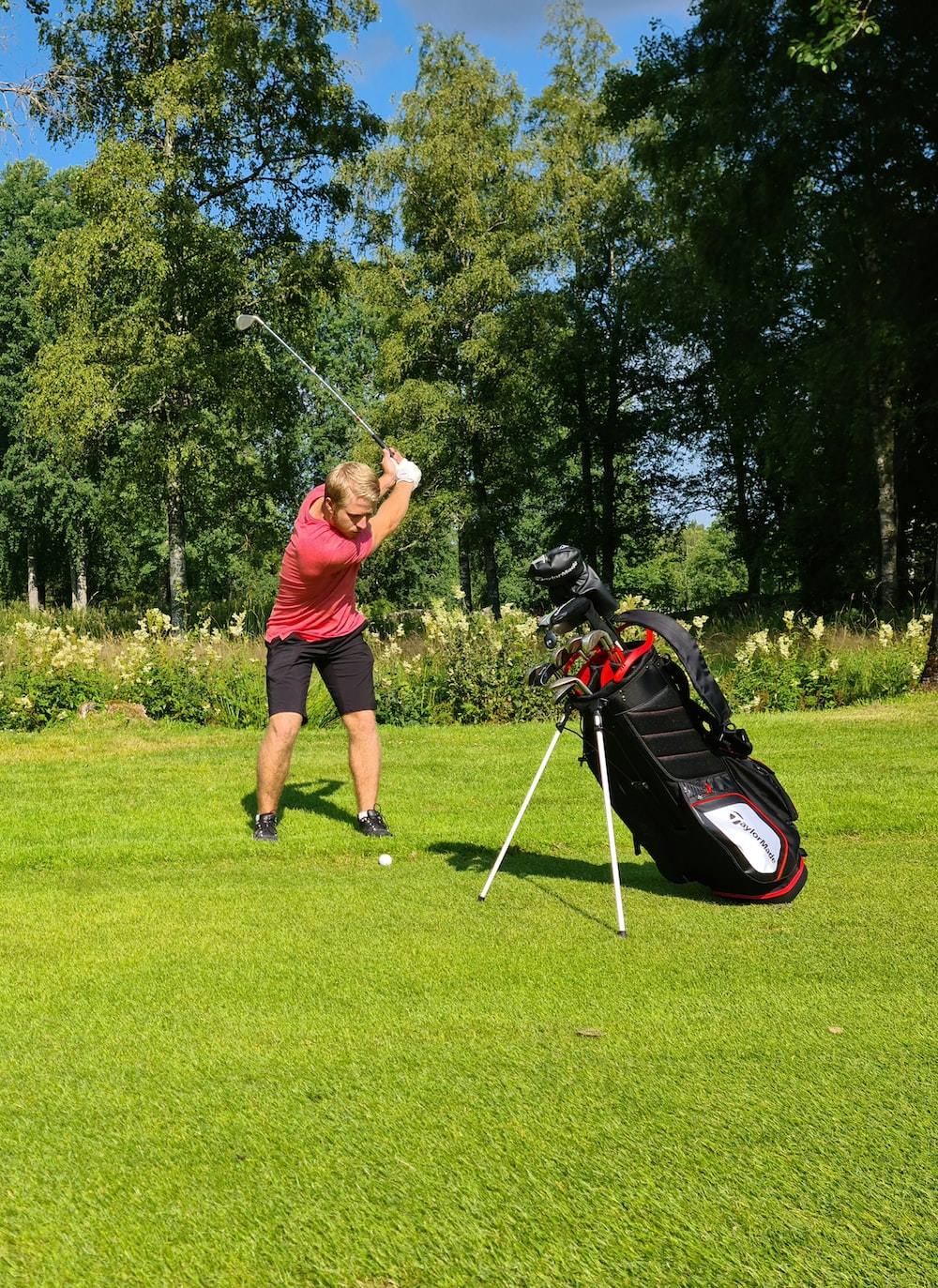 man in red t-shirt and black shorts playing golf during daytime