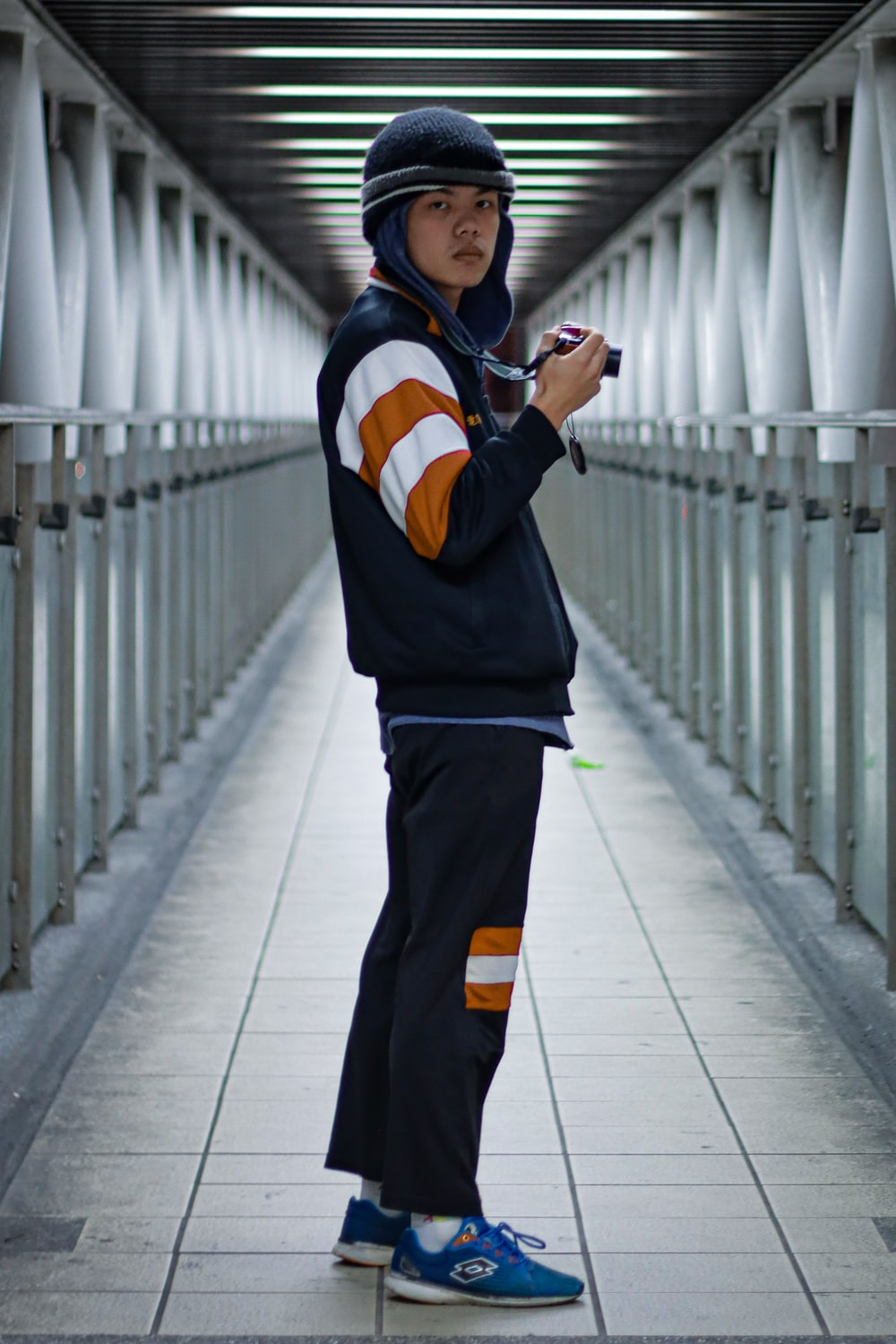 man in black and orange jacket and black pants standing on white concrete floor