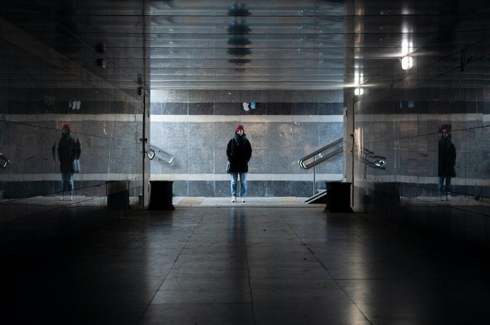 man in black jacket walking on white tiled floor