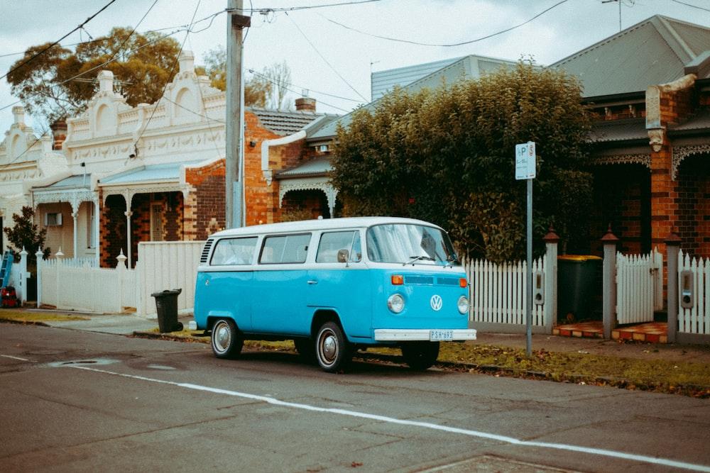 blue and white volkswagen t-2 parked on sidewalk during daytime