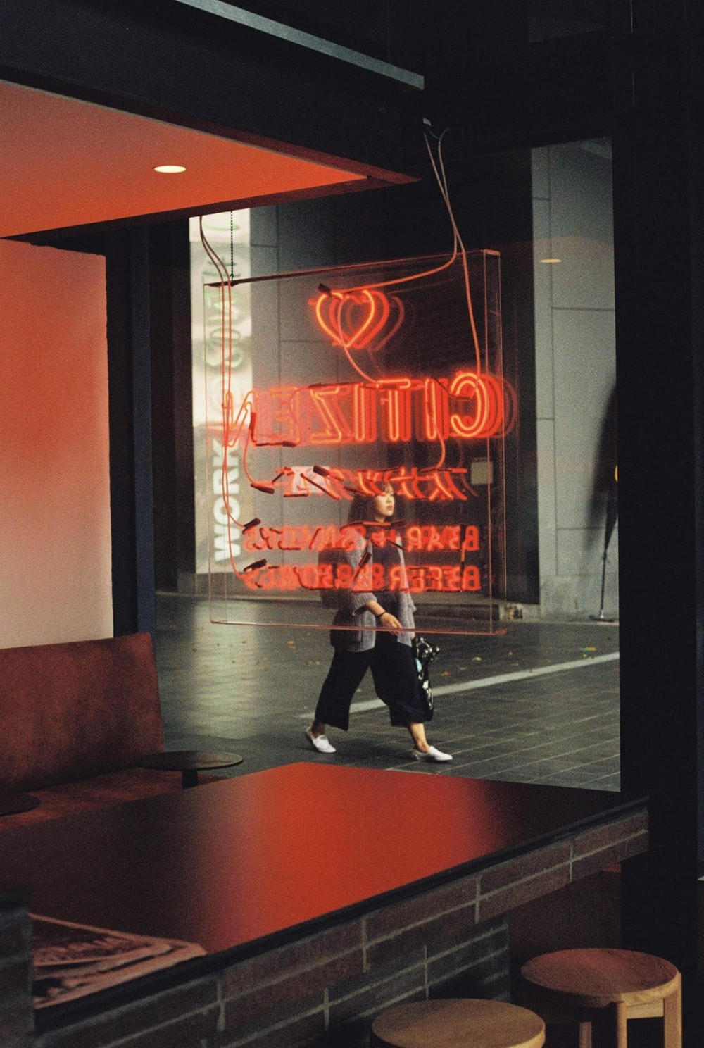 man in black jacket and black pants standing near red and white neon sign