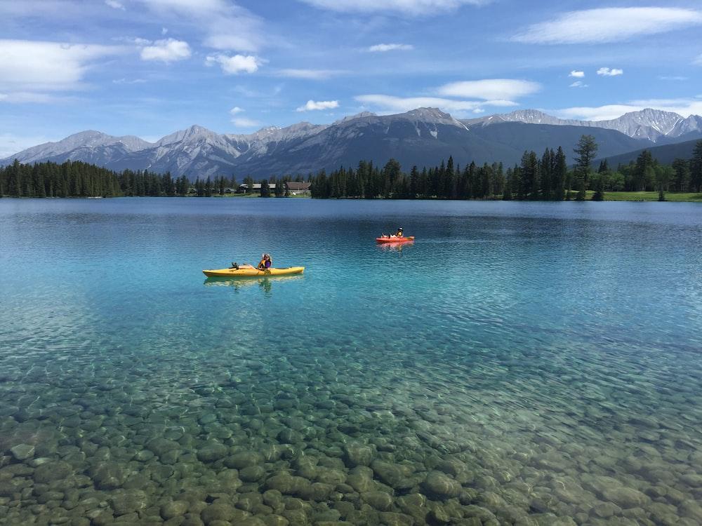 2 people riding kayak on body of water during daytime