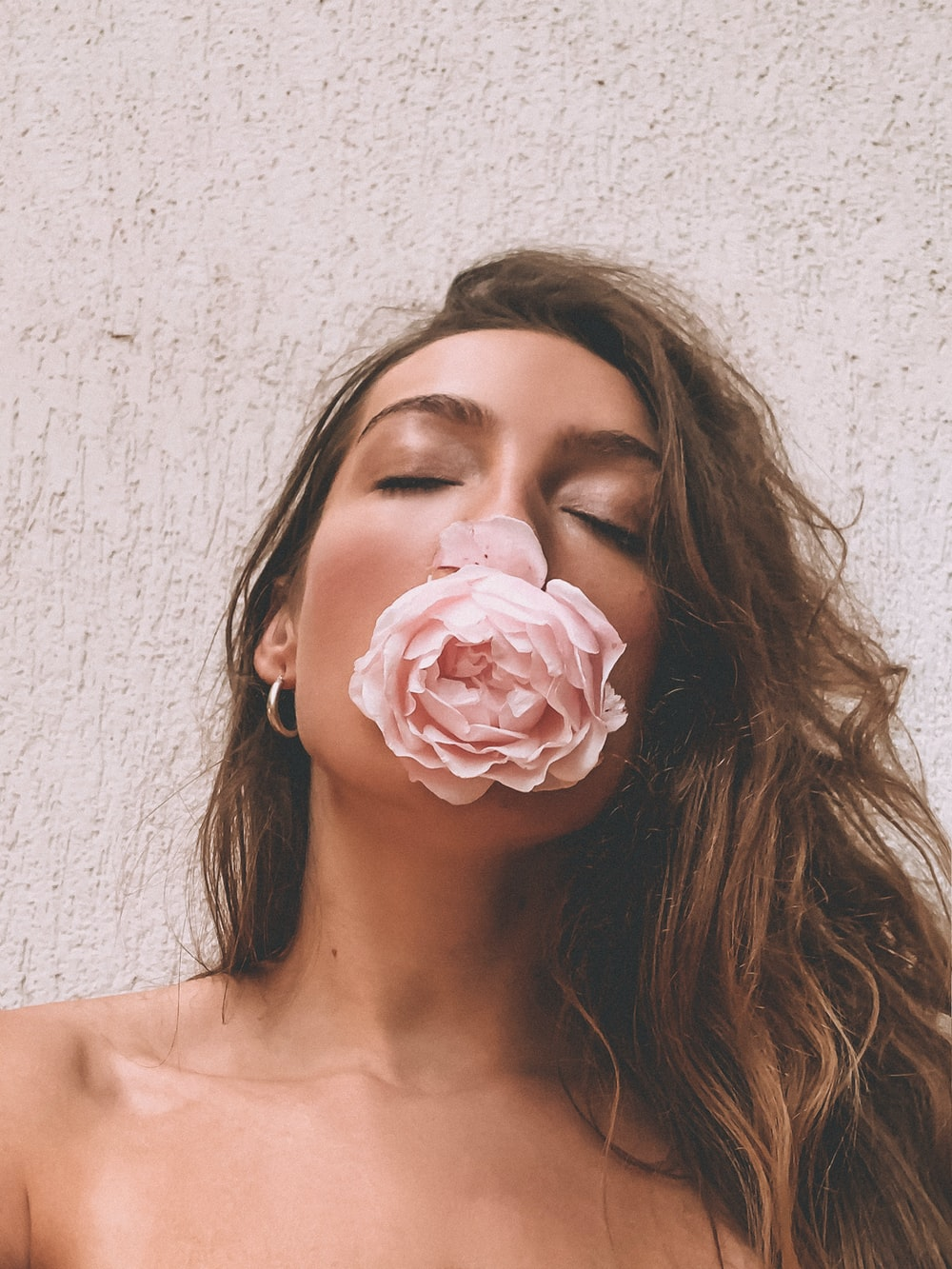 woman with pink rose on her mouth
