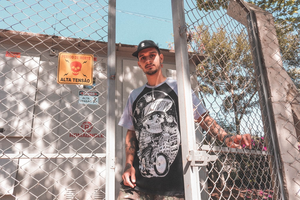 man in black and white crew neck t-shirt standing beside white metal fence during daytime