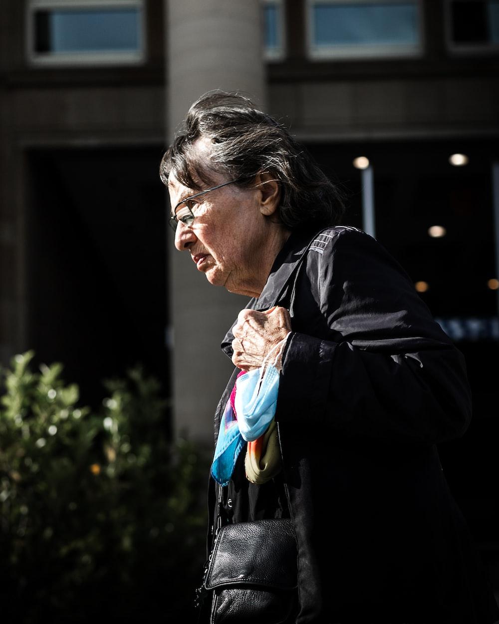 woman in black coat looking down