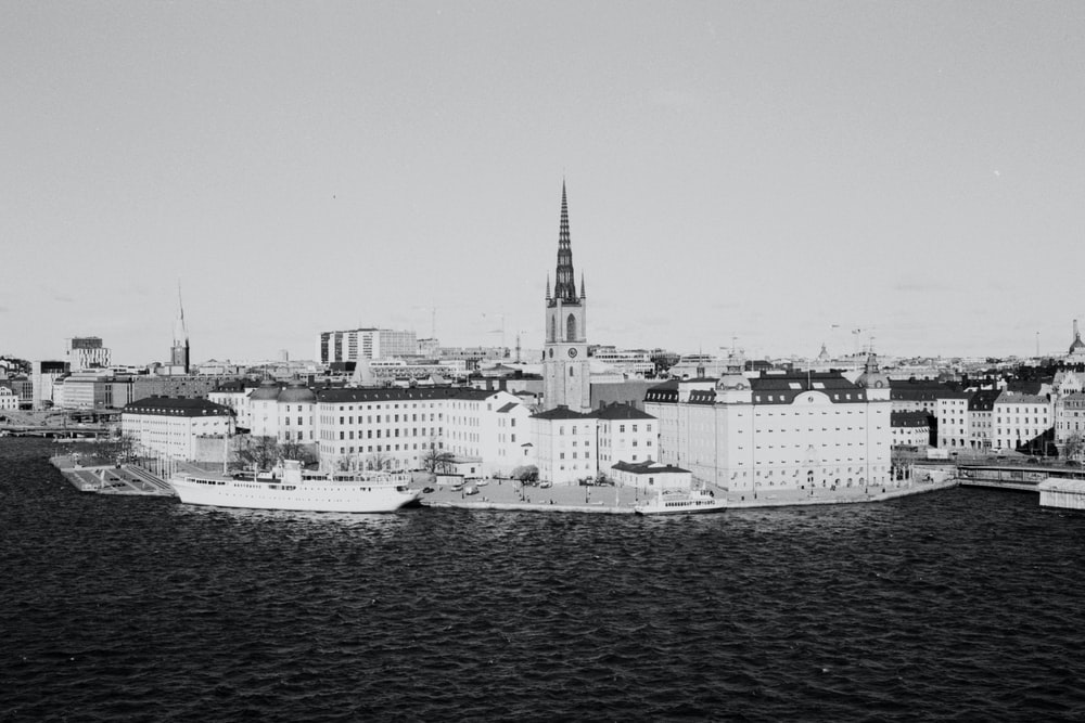 grayscale photo of city buildings near body of water