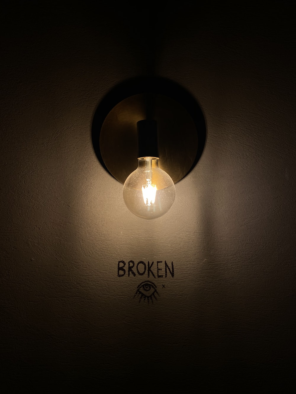 white light bulb turned on on white wall