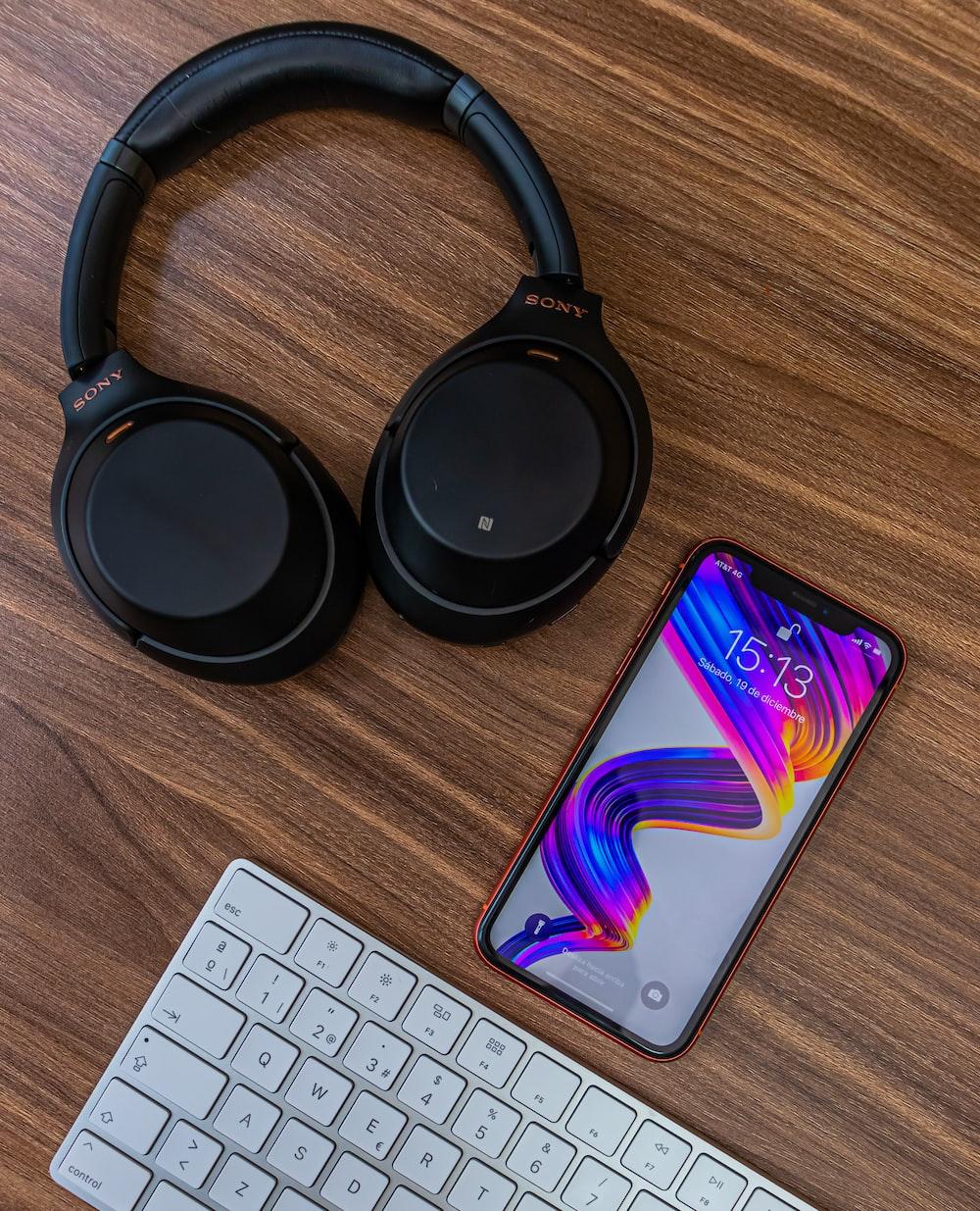 black and purple headphones beside white computer keyboard