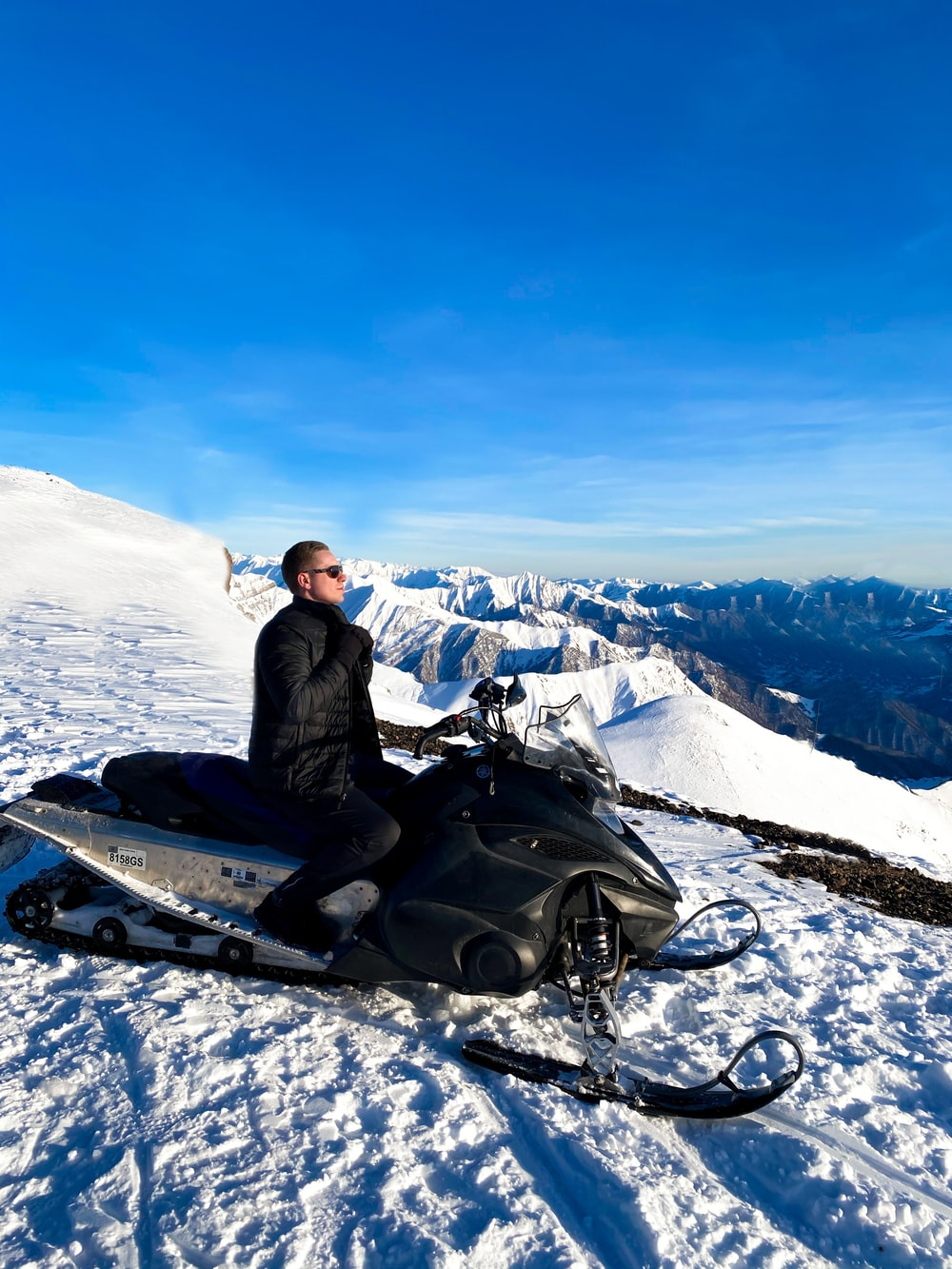 man in black jacket sitting on snow covered ground during daytime