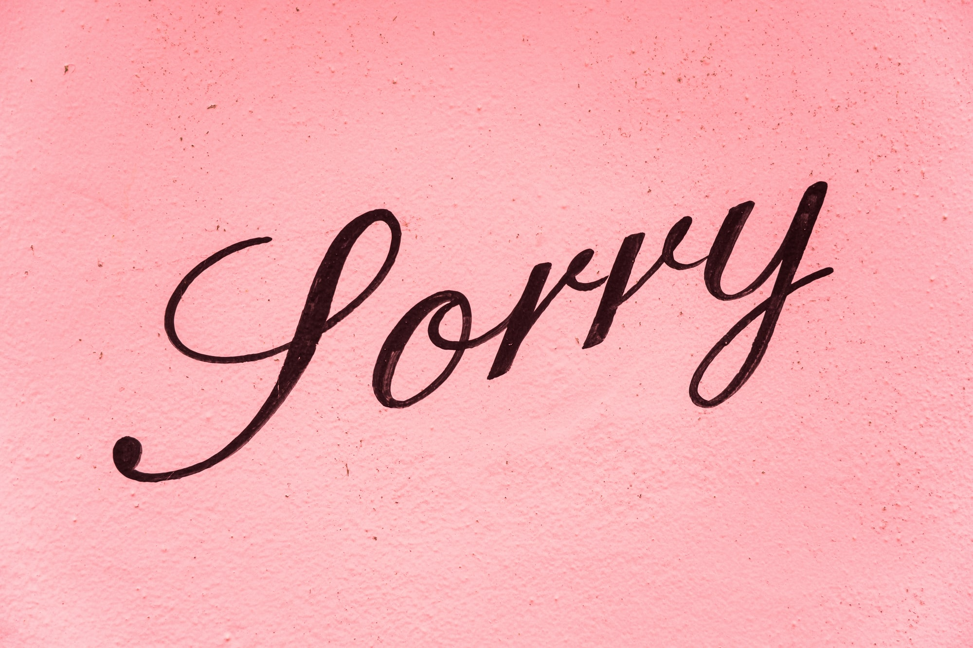 A sign saying sorry on a pink background.