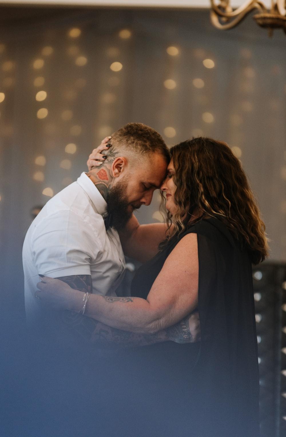 man in white dress shirt kissing woman in black sleeveless dress