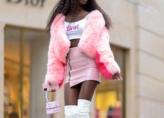 woman in pink fur coat and white pants walking on sidewalk during daytime