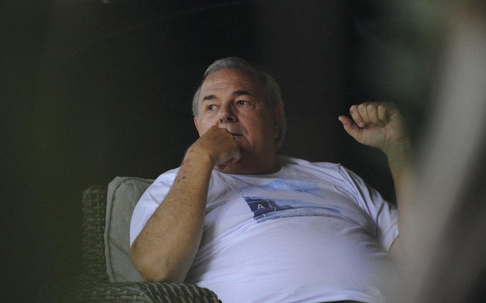 man in white crew neck t-shirt sitting on green sofa