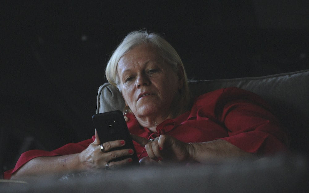woman in red long sleeve shirt holding black smartphone