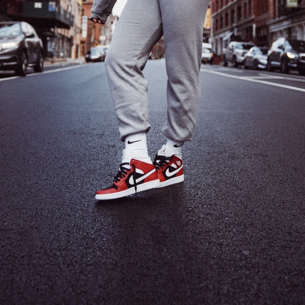 person in gray pants and red nike sneakers standing on gray asphalt road during daytime