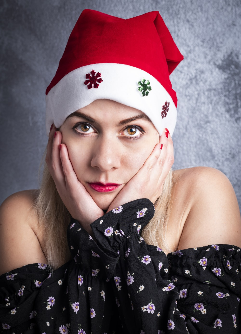 woman in black and white floral tube dress wearing red and white santa hat