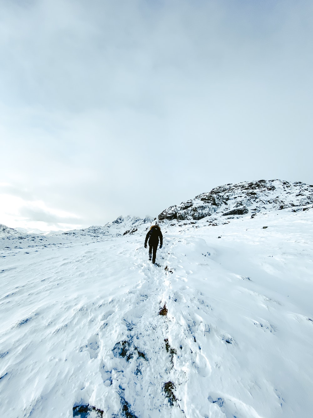 person in black jacket standing on snow covered mountain during daytime