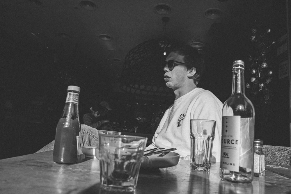 grayscale photo of man in dress shirt sitting beside table with bottles and drinking glasses