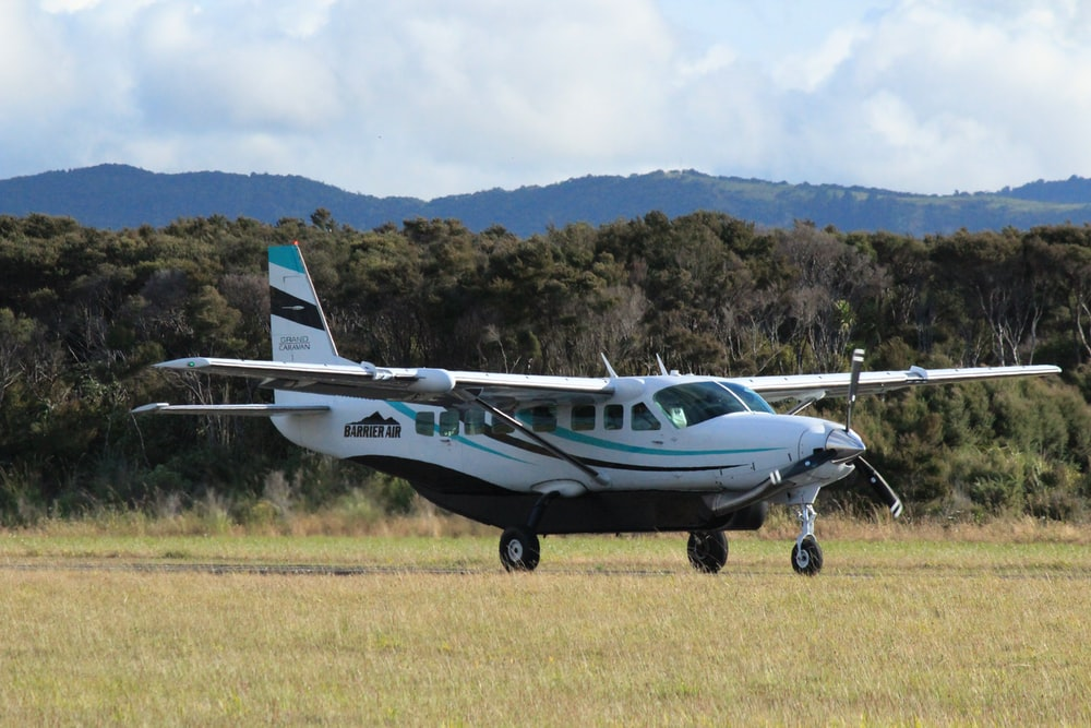 white and blue airplane on green grass field during daytime
