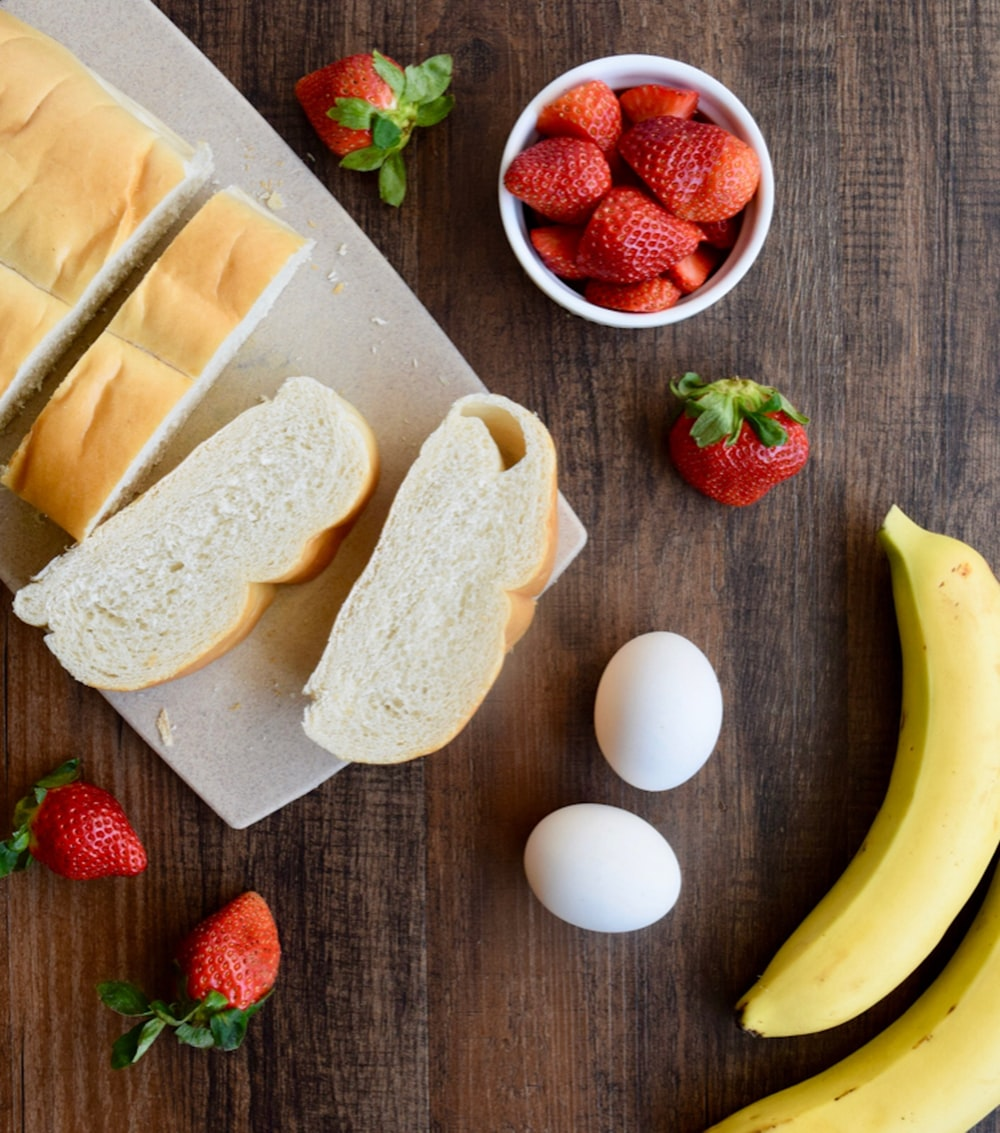 sliced bread on brown wooden chopping board beside yellow banana and red strawberries