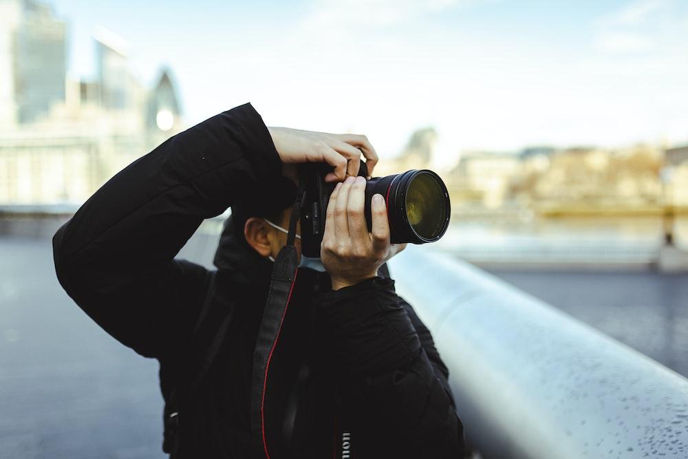 person in black jacket holding black dslr camera during daytime