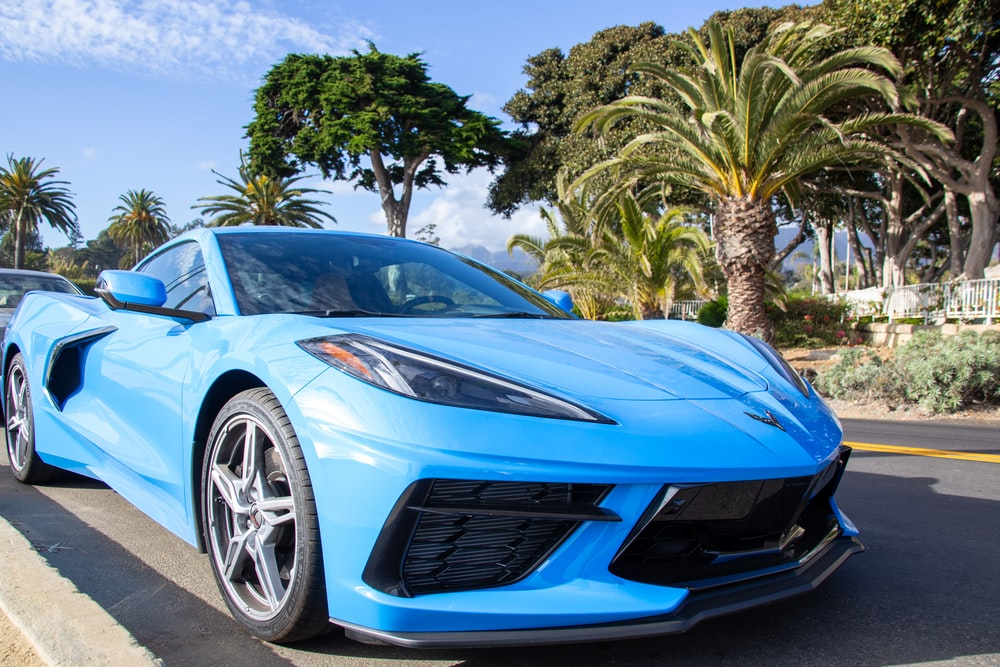 blue ferrari 458 italia parked near palm trees during daytime