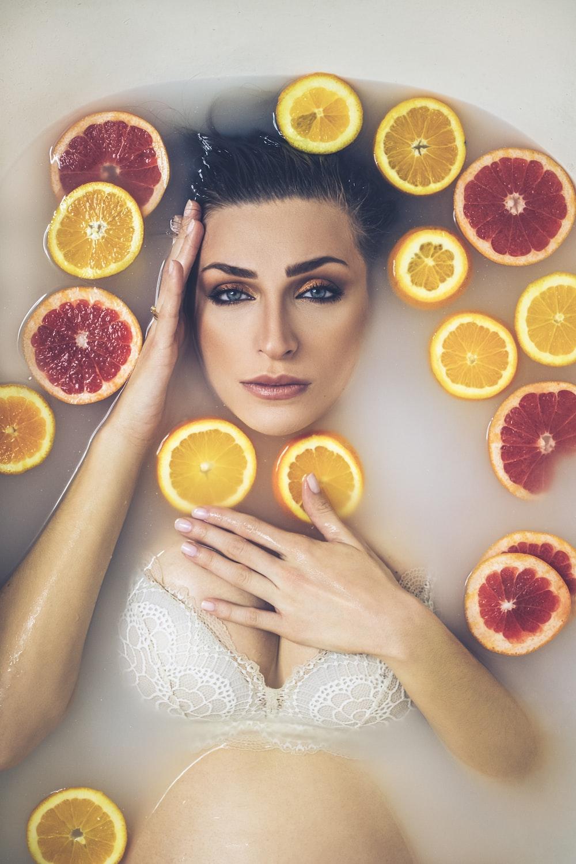 woman in white tank top holding sliced orange fruit