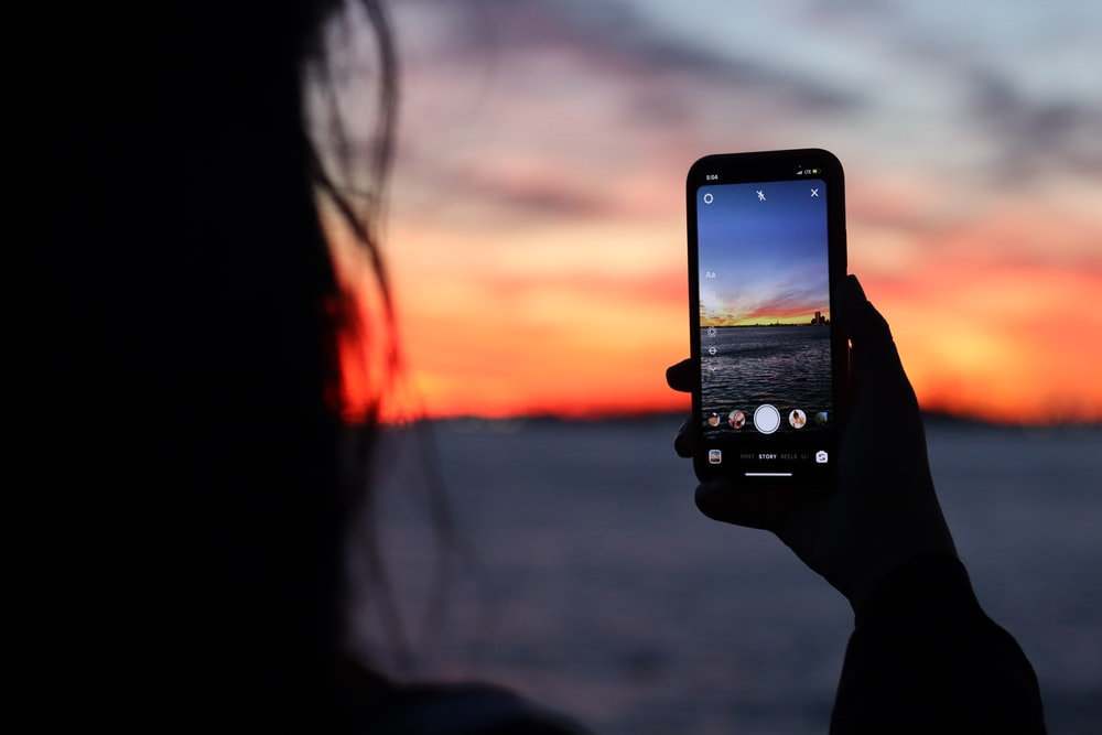 person holding black iphone 5 taking photo of sunset