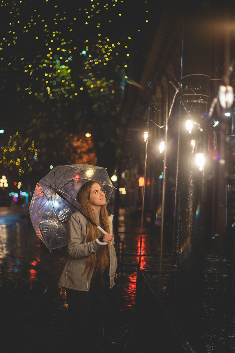 woman in brown coat holding umbrella during night time