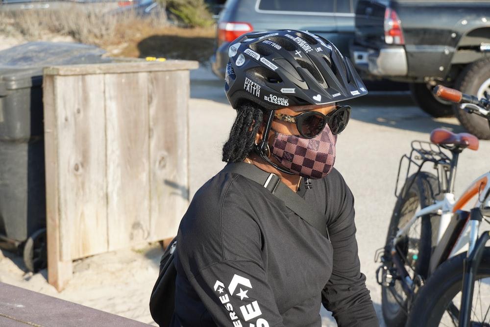 man in black jacket wearing black helmet and black helmet