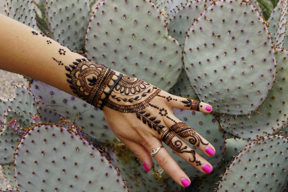 person with black and red tribal tattoo on left hand